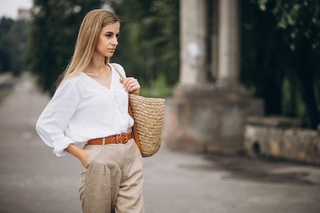 Donna bionda graziosa nello sguardo d'uso di estate del parco