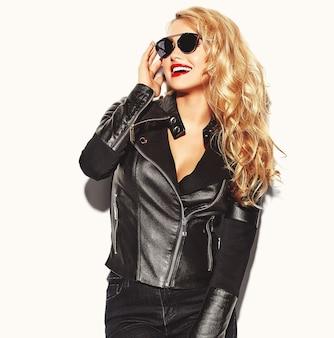 Donna bionda in abiti casual neri con labbra rosse e occhiali da sole