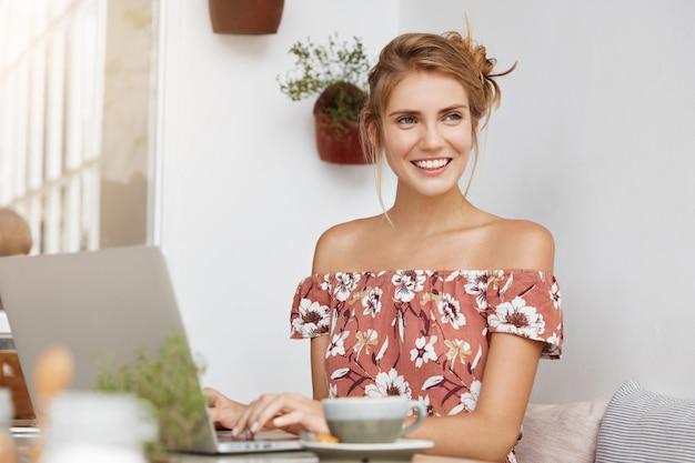 Donna bionda in abito floreale nella caffetteria