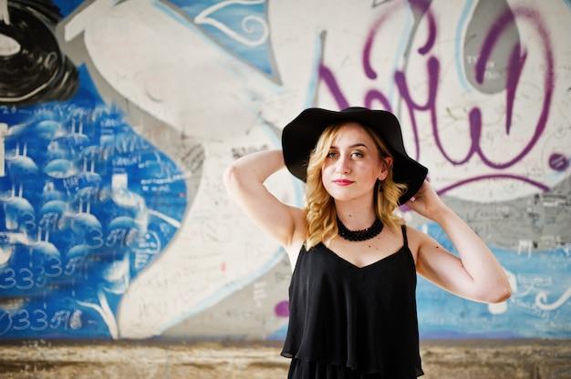 Donna bionda in abito nero, collane e cappello contro il muro di graffiti.