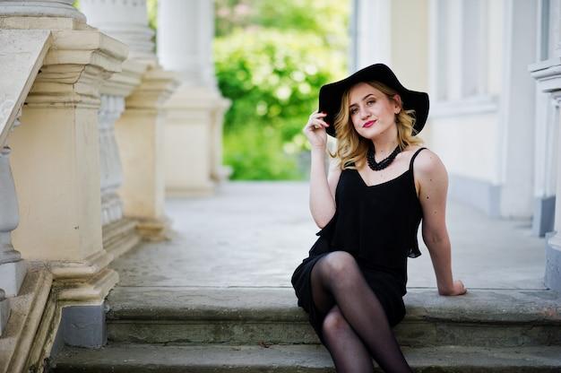 Donna bionda in abito nero, collane e cappello contro la casa d'epoca.