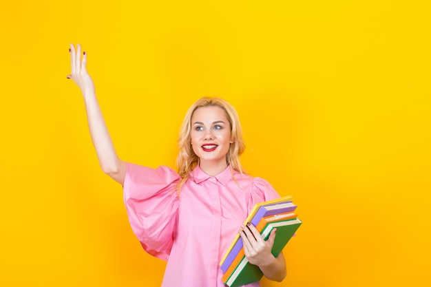 Donna bionda in camicetta rosa con una pila di libri
