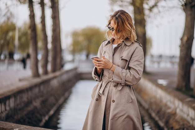 Donna bionda in cappotto fuori nel parco