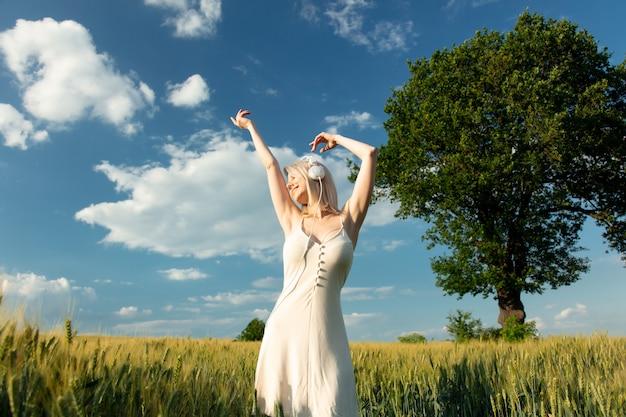 Donna bionda in cuffie che ballano nel campo di frumento nell'ora legale