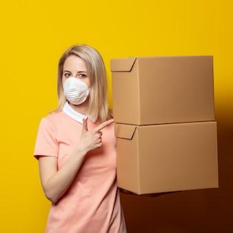 Donna bionda in maschera con scatole di consegna sul muro giallo