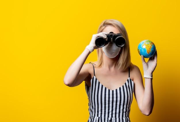 Donna bionda in maschera e guanti detiene il globo terrestre e il binocolo