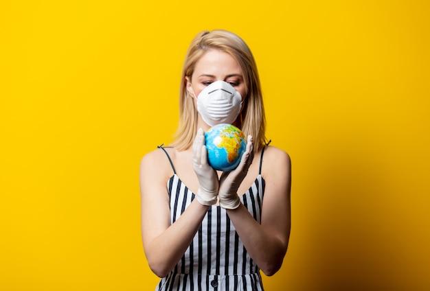 Donna bionda in maschera e guanti detiene il globo terrestre