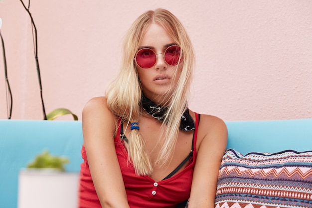 Donna bionda in occhiali da sole alla moda, indossa abiti alla moda e occhiali da sole rossi, si siede contro il muro rosa su un comodo divano.
