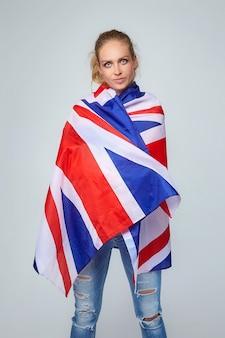 Donna bionda. in posa con la bandiera del regno unito