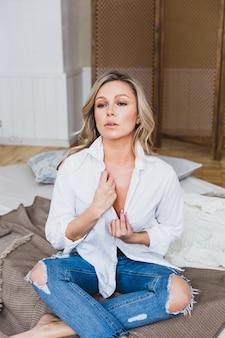 Donna bionda in una camicia bianca che si siede su un letto