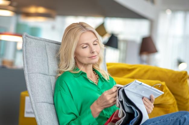 Donna bionda in una camicia verde seduto su una poltrona, guardando e toccando campioni di tessuto in un salone di mobili, pensieroso.