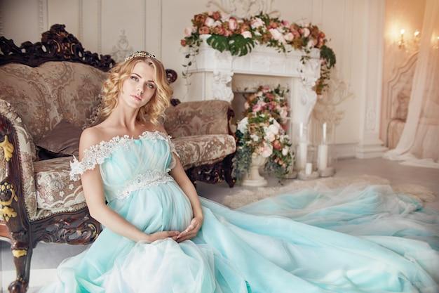 Donna bionda incinta di modo di lusso in un vestito da cerimonia nuziale.