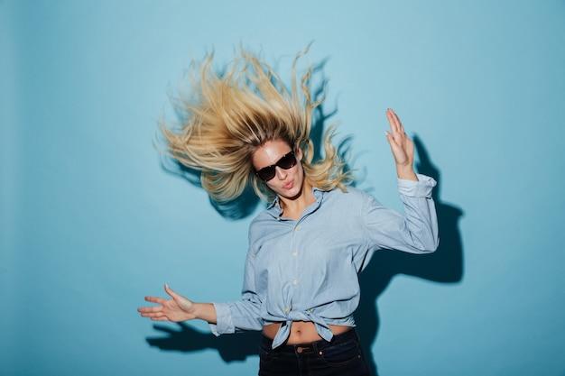 Donna bionda insolita in camicia e occhiali da sole che guarda l'obbiettivo