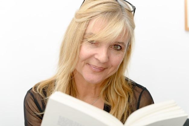Donna bionda matura che legge un libro