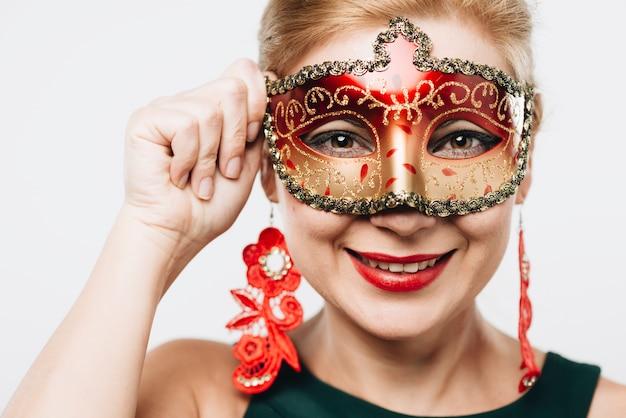 Donna bionda nella maschera di carnevale rosso brillante