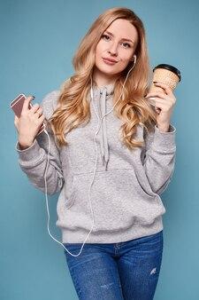 Donna bionda positiva sveglia in maglia con cappuccio con il telefono e il caffè