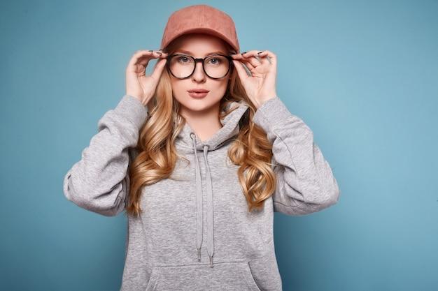 Donna bionda positiva sveglia in un berretto da baseball rosa