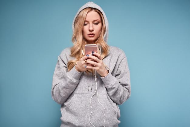 Donna bionda positiva sveglia nella musica d'ascolto di maglia con cappuccio