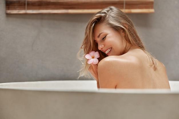 Donna bionda rilassante nella vasca da bagno con petali