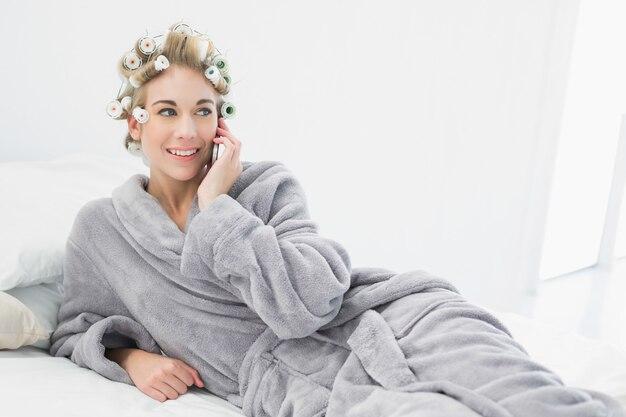 Donna bionda rilassata allegra in bigodini che chiama con il suo telefono cellulare