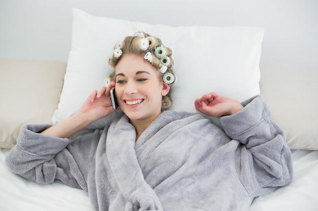 Donna bionda rilassata contentissima in bigodini che fanno una telefonata