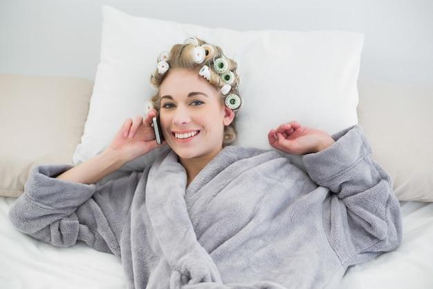 Donna bionda rilassata sveglia in bigodini che chiama con il suo telefono cellulare