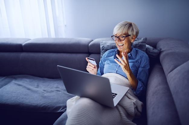 Donna bionda senior affascinante allegra con i capelli corti e con gli occhiali che si siedono sul sofà in salone, tenendo il computer portatile in grembo e usando la carta di credito per lo shopping online