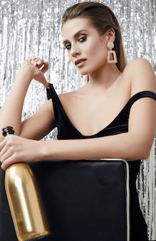 Donna bionda sensuale elegante in vestito nero con una bottiglia di champagne