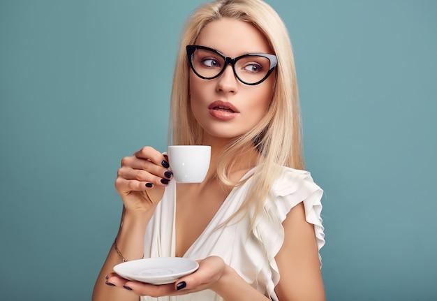 Donna bionda sensuale splendida in vestito bianco con la tazza di caffè