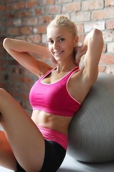 Donna bionda sexy che riposa dopo l'esercizio.
