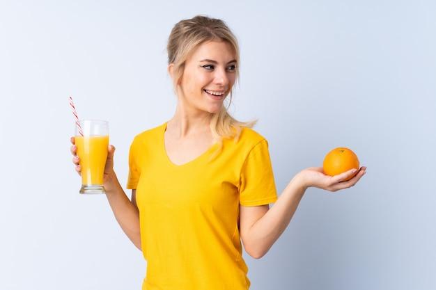 Donna bionda sopra il blu isolato che tiene un'arancia e un succo d'arancia