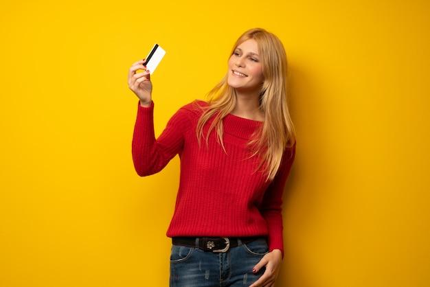 Donna bionda sopra la parete gialla con lo smartphone rotto azienda disturbata