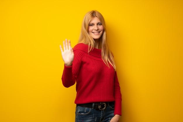 Donna bionda sopra muro giallo salutando con la mano con espressione felice