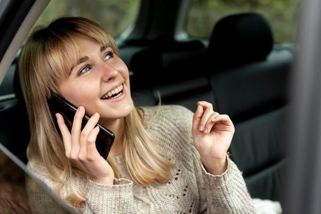 Donna bionda sorridente che parla sul telefono
