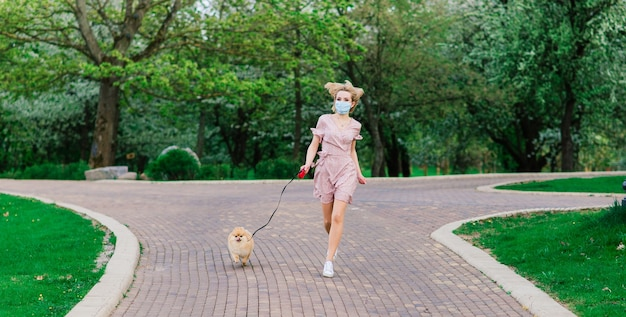 Donna bionda sorridente con il suo cane di pomerania nel parco