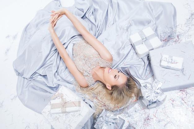Donna bionda sorridente felice in vestito d'argento lungo con scatole regalo e coriandoli che cadono