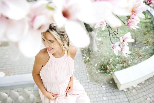 Donna bionda sorridente in vestito che si siede sotto l'albero