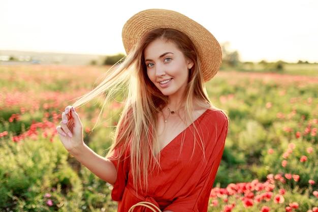 Donna bionda spensierata giocosa in posa volentieri mentre cammina fuori di buon umore. indossa un cappello di paglia, tuta arancione. campo di papaveri.