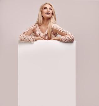 Donna bionda splendida che tiene un tabellone per le affissioni in bianco