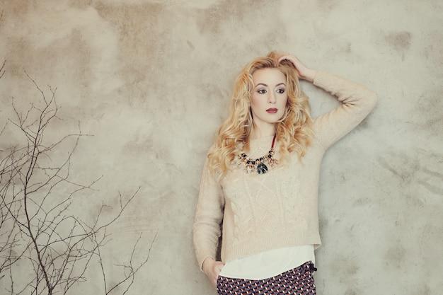 Donna bionda splendida in maglione beige