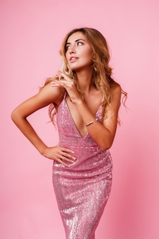 Donna bionda stupita con la posa dei capelli ventosi. muro rosa. modello splendido. emozioni estatiche.