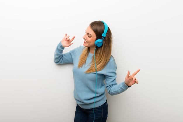 Donna bionda su sfondo bianco isolato ascoltando musica con le cuffie e ballare