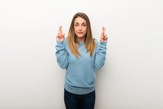 Donna bionda su sfondo bianco isolato con le dita che attraversano e che desiderano il meglio