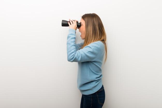 Donna bionda su sfondo bianco isolato e guardando in lontananza con il binocolo