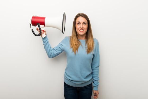 Donna bionda su sfondo bianco isolato prendendo un megafono che fa un sacco di rumore