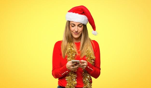 Donna bionda vestita per le vacanze di natale inviando un messaggio o e-mail con il cellulare