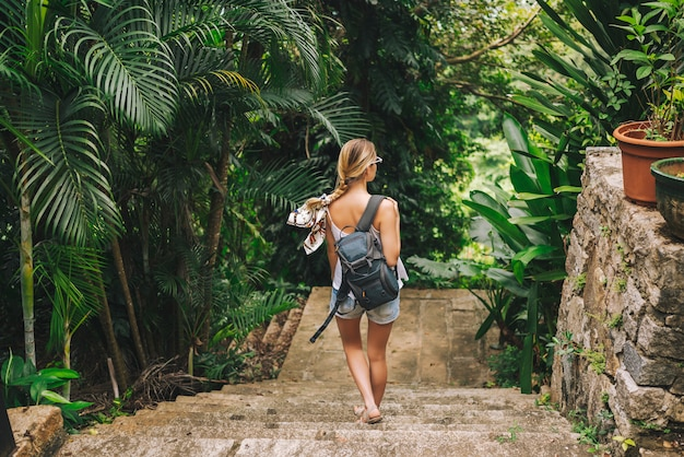 Donna bionda viaggiatore con zaino e sacco a pelo che cammina e che scopre il parco tropicale della giungla, natura di avventura di viaggio in cina, bella destinazione turistica asia, concetto di viaggio di viaggio di vacanze estive di vacanza