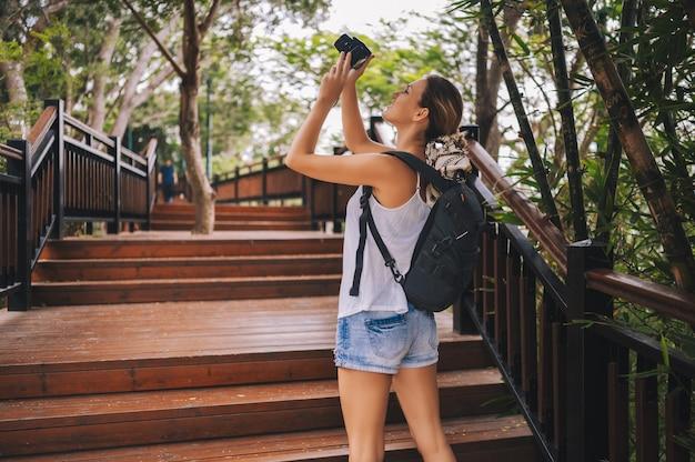 Donna bionda viaggiatore con zaino e sacco a pelo che cammina prendendo foto in un parco tropicale, viaggi avventura natura in cina, bella destinazione turistica asia, viaggio vacanze estive, copia spazio per banner