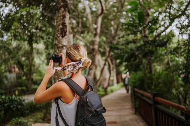 Donna bionda viaggiatore con zaino e sacco a pelo che cammina prendendo foto nella foresta tropicale, viaggi avventura natura in cina, bella destinazione turistica asia, viaggio vacanze estive, copia spazio per banner