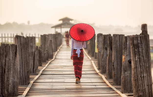 Donna birmana che tiene ombrello rosso tradizionale e che cammina sul ponte u bein